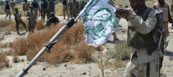 A Nigerian soldier pull down a Boko Haram flag as a mark of victory