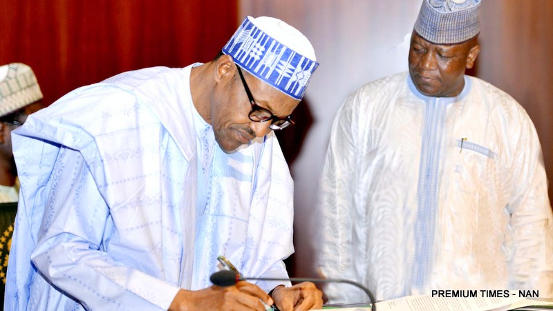PIC. 28. PRESIDENT MUHAMMADU BUHARI SIGNING A DOCUMENT ON NIGERIA'S COMMITMENT TO ERADICATE POLIO, AT THE PRESIDENTIAL VILLA IN ABUJA ON WEDNESDAY (20/01/16). WITH HIM IS THE CHAIRMAN OF NIGERIA GOVERNORS ' FORUM, GOV. ABDULLAZIZ YARI OF ZAMFARA. 0345/20/1/2016/ISE/HB/BJO/NAN