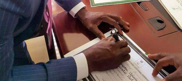 Ogah appending his signature to a document at INEC office